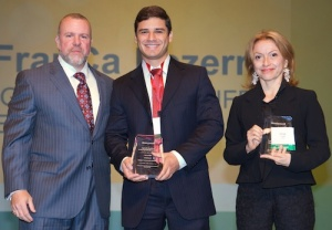 Andrew D'Amelio - vice president of sales in the Americas for Honeywell Process Solutions - presents the 2014 UniSim Design Challenge Award to student Herbert Senzano Lopes and Prof. Vanja Maria de Franca Bezerra of the Federal University of Rio Grande do Norte (Brazil).